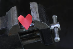 Heart Attack. Small red paper heart under pressure with old vise grip on dark background Stock Photo