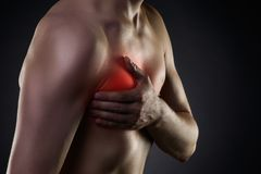 Heart attack, man with chest pain on black background Stock Photos