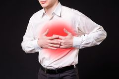Heart attack, man with chest pain on black background. With red dot stock image