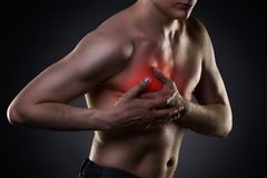 Heart attack, man with chest pain on black background Royalty Free Stock Images
