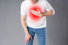 Heart attack, man with chest pain on gray background royalty free stock photos