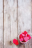 Heart background. Copyspace old wooden background with small pink bucket with red hearts Stock Image