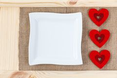 Heart on a background of wood covered with burlap, white square plate a card for Valentine`s Day. With some free space for your text or sign. Valentines day Royalty Free Stock Photos
