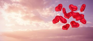 Composite image of heart balloons. Heart balloons against cloudy sky landscape Royalty Free Stock Photo