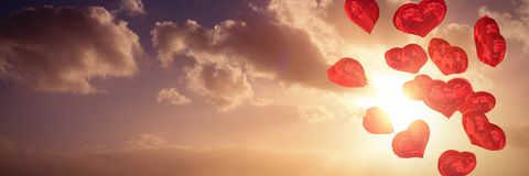Composite image of heart balloons. Heart balloons against cloudy sky landscape Stock Photography