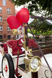 Heart balloons on vintage wedding car. Red heart-shaped balloons attached to white vintage wedding car Royalty Free Stock Image