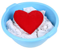 Heart in a basin. Red heart in a blue basin with dirty laundry Royalty Free Stock Photos