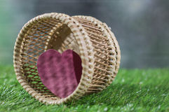 Heart in basket in green grass background royalty free stock photography