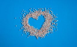 Heart of bath pearls on a blue background royalty free stock photo