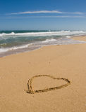 Heart on the beach. A loveheart drawn on the sand at the beach Stock Image