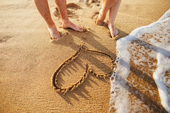 Heart on the beach. With couple foots close up with sea wave Stock Image