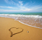 Heart on beach. Heart on the sand of a beach. Romantic composition Stock Photos