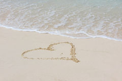 Heart in beach sand with wave Royalty Free Stock Photo