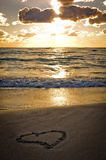 A heart on the beach at sunset. A heart waiting for you on the beach by the sea lit by the sunset Stock Image