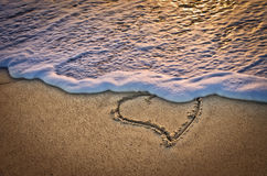 A heart on the beach at sunset. A heart waiting for you on the beach by the sea lit by the sunset Royalty Free Stock Image