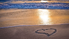 A heart on the beach at sunset. A heart waiting for you on the beach by the sea lit by the sunset Stock Photography