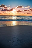 A heart on the beach at sunset. A heart waiting for you on the beach by the sea lit by the sunset Royalty Free Stock Photo