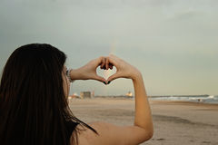 A heart in the beach. Young woman creating a heart with the hands in a beach with a rainbow in the background Royalty Free Stock Images