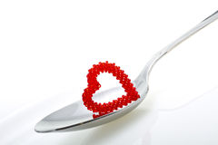 Heart of beads. Spoon and heart isolated on white royalty free stock images