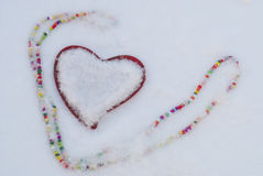 Heart and beads on the snow Royalty Free Stock Photos