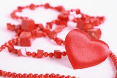 Heart and beads on white. Red heart and coral beads on white Stock Photography