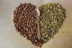 Heart of beans black coffee and green tea leaves Stock Images