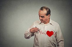 Heart beat. Middle aged man drawing Heart beats on his chest royalty free stock image