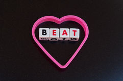 Heart beat. Text ' beat ' in uppercase letters on white cubes inside a pink heart shape making concept heart beat, on dark background Stock Image