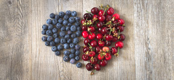 Heart of berries on a wooden table. In natural light Royalty Free Stock Images