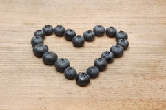 Heart of bilberries. On wooden ground Stock Photo