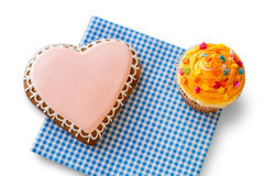 Heart biscuit and orange cupcake. Royalty Free Stock Images