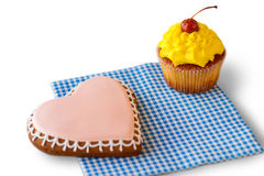 Heart biscuit and yellow cupcake. Stock Photography