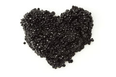 Heart of black caviar. Isolated on white Royalty Free Stock Photo