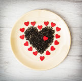 Heart of black loose tea from Ceylon and little red paper hearts Royalty Free Stock Image