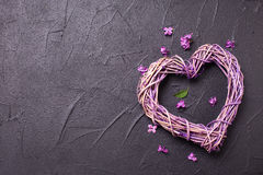 Heart on  black textured background. Decorative heart  and little lilac flowers on  black textured background. Top view. Place for text Stock Images