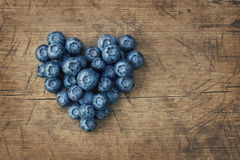 Heart from blackberries. On a wooden background stock images