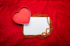 Heart with a blank card on red background Stock Images