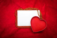 Heart with a blank card on red background Stock Photos