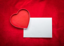 Heart with a blank card on red background Royalty Free Stock Images