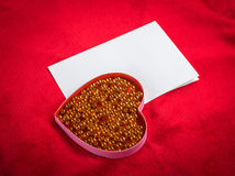 Heart with a blank card on red background Stock Image