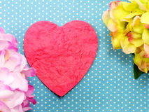 Heart on blue polka dot background and beautiful flower Stock Images