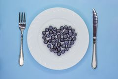 Heart of blueberries on white plate with cutlery. Love vegan diet concept. Valentine`s Day royalty free stock photo