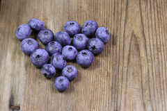 Heart of blueberry on wooden background Royalty Free Stock Image