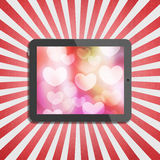 Heart bokeh on tablet display Royalty Free Stock Image