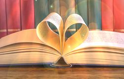 Heart and book. A open book with pages forming the heart, rank of books. s. A open book with pages forming the heart, rank of books. Light effects royalty free stock image