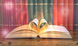 Heart and book. A open book with pages forming the heart, rank of books. A open book with pages forming the heart, rank of books. Light effects stock images