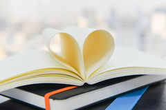 Heart from the book pages. On stack of books stock photo