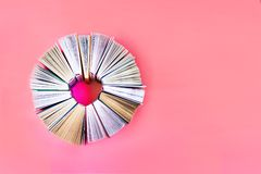 The heart of books on coral background. Top view. Love story books. Copy space stock image