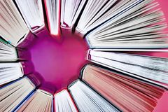 The heart of books on pink background. Top view. Love reading stock image