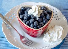Heart  bowl of fresh blueberries with cream. A red heart bowl of fresh Blueberries is on a blue plank background and garnished with whipped cream Royalty Free Stock Photography